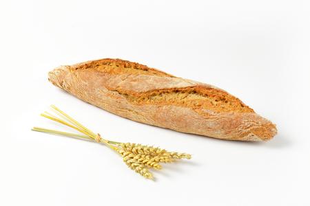 whole grain: long loaf of whole grain bread and grain ears