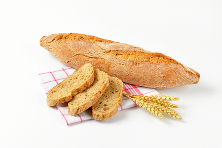 whole grain: long loaf and slices of whole grain bread