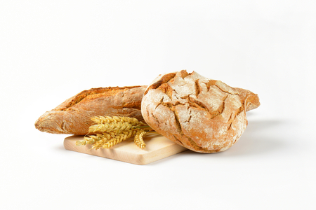 freshly baked bread and baguette on wooden cutting board