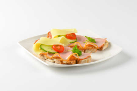 two faced: two open faced sandwiches with ham and cheese on white plate