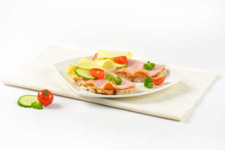 two faced: two open faced sandwiches with ham and cheese on white plate and place mat Stock Photo