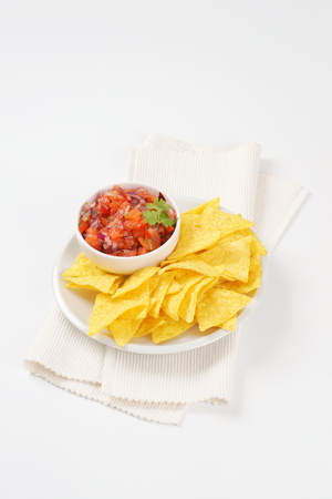 cruda: tortilla chips and bowl of salsa fresca on white plate