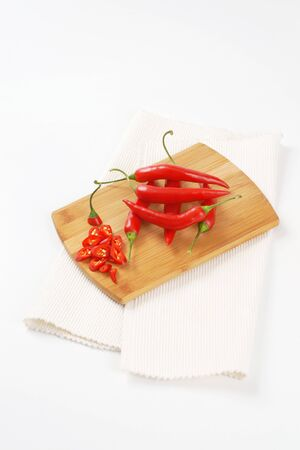 chili peppers: whole and sliced chili peppers on wooden cutting board