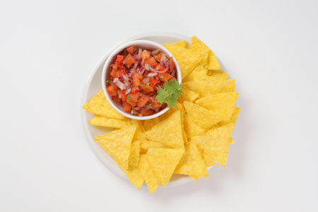 tortilla chips: bowl of salsa fresca and tortilla chips on white plate