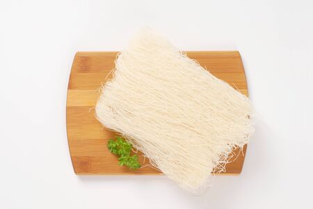 rice noodles: bundle of dried rice noodles on cutting board Stock Photo