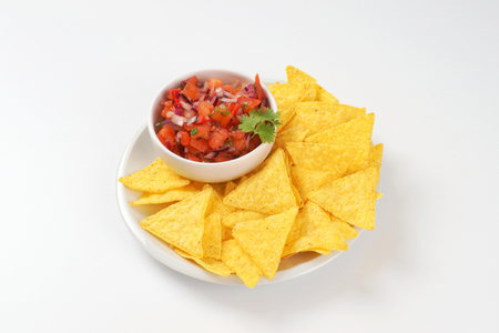 cruda: bowl of salsa fresca and tortilla chips on white plate