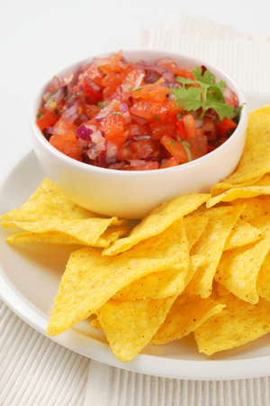 tortilla chips and bowl of salsa fresca on white plate
