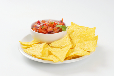 triangle shaped: bowl of salsa fresca and tortilla chips on white plate