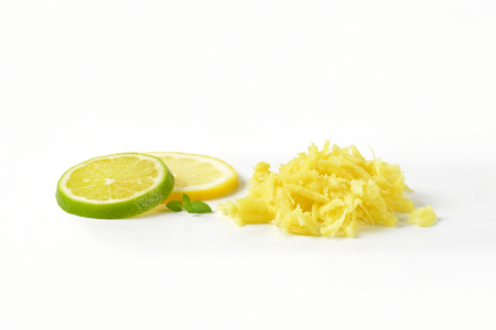 grated fresh ginger and slices of lime and lemon on white background