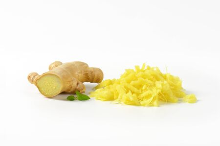 whole and grated fresh ginger on white background