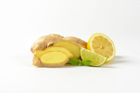 lemon wedge: fresh ginger root with lemon and lime on white background