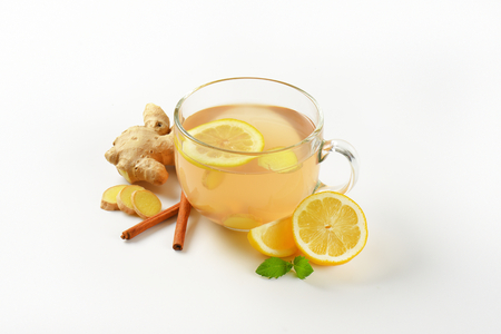 ginger tea: cup of ginger tea with lemon, fresh ginger root and cinnamon sticks on white background Stock Photo