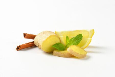 cinnamon sticks: sliced ginger with lemon and cinnamon sticks on white background