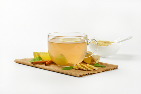 ginger tea: cup of ginger tea with lemon, fresh ginger root and cinnamon sticks on brown place mat