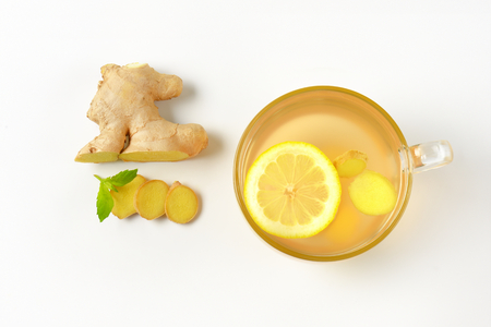 ginger tea: cup of ginger tea with lemon and pieces of fresh ginger root next to it Stock Photo