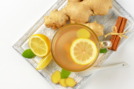 ginger tea: cup of ginger tea with lemon, fresh ginger root and cinnamon sticks on wooden cutting board