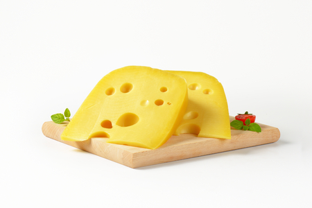 swiss cheese: two wedges of Swiss cheese on wooden cutting board