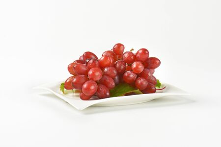 washed: bunch of washed red grapes on white plate