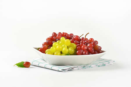 dishtowel: bowl of red and white grapes on checkered dishtowel Stock Photo