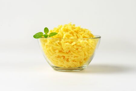 bowl of grated cheese on white background