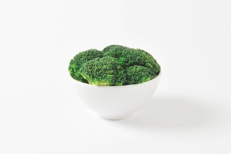 florets: Raw broccoli florets in white bowl