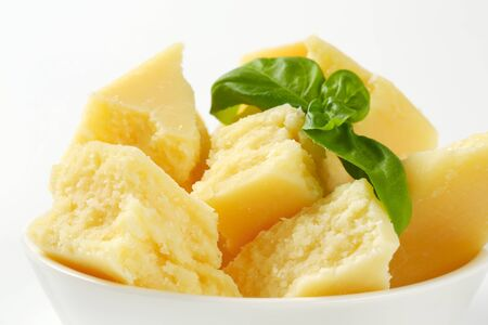 Parmesan: Pieces of Parmesan cheese in a bowl Stock Photo