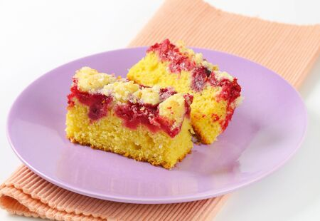 crumb: Pieces of raspberry crumb cake on purple plate