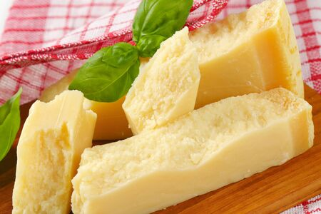 Parmesan: Pieces of Parmesan cheese on cutting board