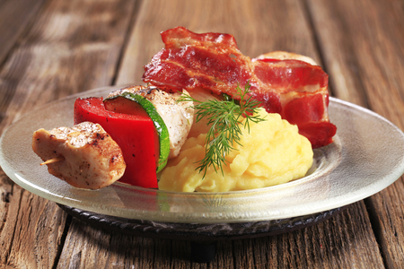 Chicken shish kebab with mashed potato and rasher of bacon