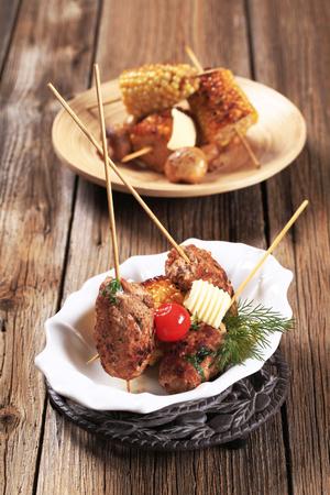 sweetcorn: Minced meat kebabs on wooden skewers and roasted sweetcorn