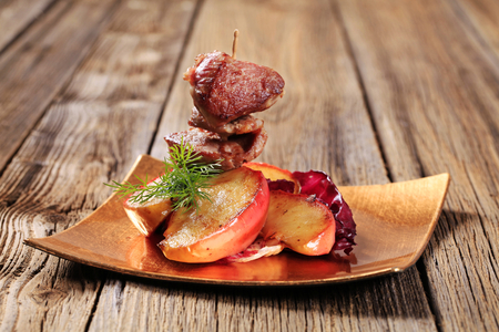 baked meat: Roasted meat on stick and slices of apple