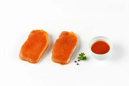 pork chops: raw honey glazed pork chops on white background