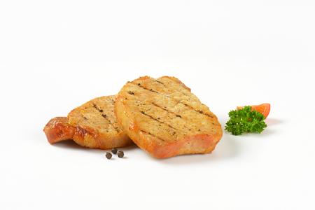 pork chops: Two grilled honey glazed pork chops on white background