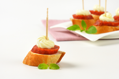 Bread based canapes with spicy sausage and creamy spread Stock Photo