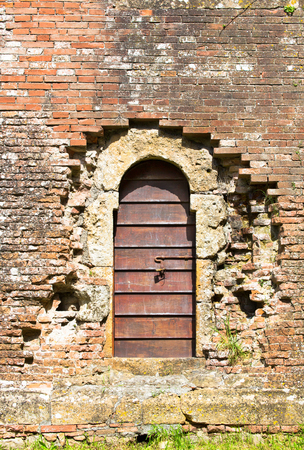 worn structure red: Arched entrance with old wooden door in aged brick wall Stock Photo