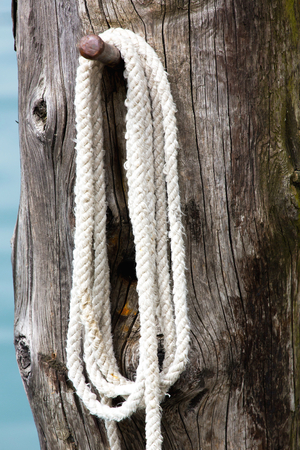 wooden post: White mooring rope on wooden post