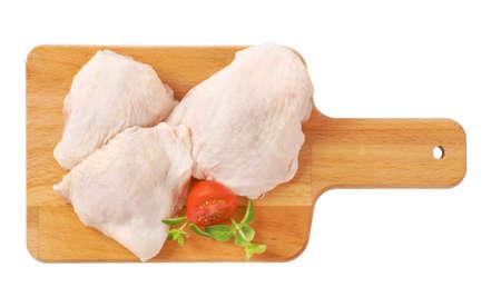 muslos: muslos de pollo cruda en la tabla de cortar de madera