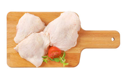 muslos: raw chicken thighs on wooden cutting board