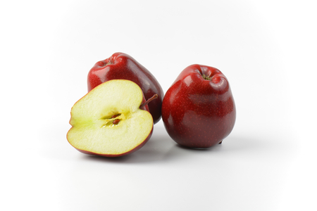 halved  half: Two and a half red apples on off-white background