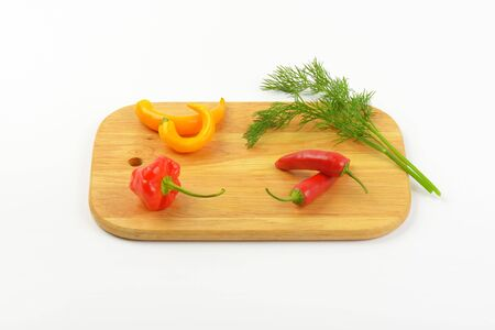 chili peppers: fresh chili peppers and dill on wooden cutting board Stock Photo