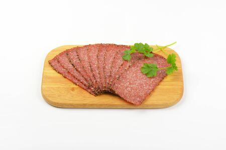 pepper salami: Thin slices of pepper coated salami on wooden cutting board