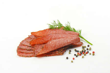 pepper salami: Thin slices of black pepper salami with peppercorns on white background