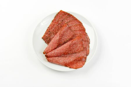 pepper salami: Thin slices of pepper coated salami on white plate