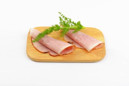 two ham slices with dill on wooden cutting board