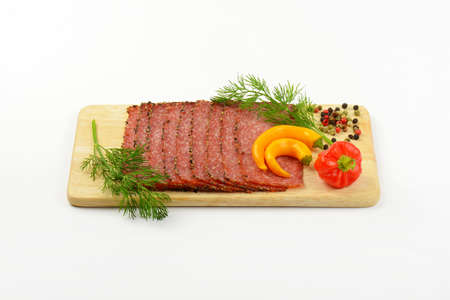 pepper salami: Black pepper salami slices with peppercorns and chili peppers on wooden cutting board Stock Photo