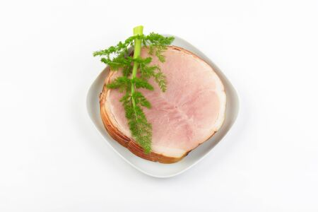 stack of ham slices and dill on white plate