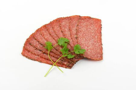 pepper salami: Thin slices of pepper coated salami on white background
