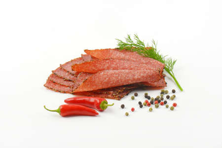 Thin slices of black pepper salami with peppercorns and red chili peppers Stock Photo