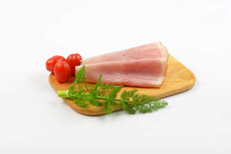 ham slices with dill an cherry tomatoes on wooden cutting board Stock Photo