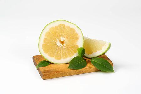 halved  half: green grapefruit half and slice on cutting board Stock Photo